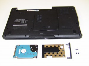 Remove the (2) 3mm x 3mm screws holding the 1545 hard drive cage and bezel and lift off of the hard drive.