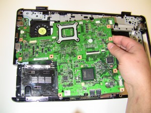 The motherboard part number is located on the front of the motherboard under the touchpad palm rest.