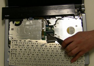 Unscrew the (2) 2mm x 3mm screws holding the keyboard to the base and gently flip the keyboard over. Be cautious, lifting the keyboard with the cable connected, it is possible to break the latch if you pull it too hard.