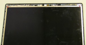 Remove the (2) 2.5mm x 5mm screws on the bottom left and right of the screen.