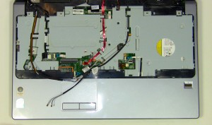On the top of the laptop, pull the antenna cables through the motherboard and loosen them from the routing channels on the palm rest.