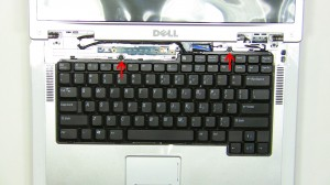 Carefully lift the keyboard up and place it onto the LCD screen to reveal the keyboard cable connection.