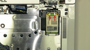 Press the wireless card latch up until the card pivots up at a 45 degree angle.