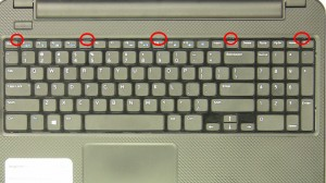 Using a plastic scribe or flat head screwdriver, press in the keyboard latches at the top of the keyboard.