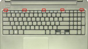 Press in the keyboard latches and carefully turn the keyboard over.