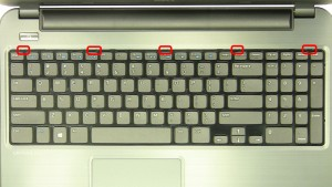 Press the keyboard locking tabs in to loosen the keyboard.