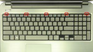Press the keyboard locking tabs in to loosen the keyboard.
