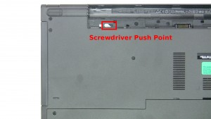 Use the slot under the battery to slide the optical drive out.