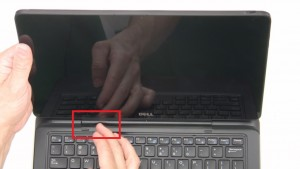 Slide button to the left to unlock tablet from base.