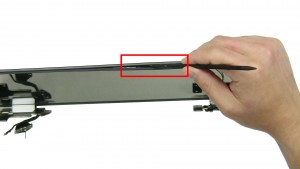 Using a plastic scribe, unsnap the back cover around the edges of the screen.