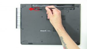 Using a plastic scribe, push to release DVD Drive from the optical drive bay.